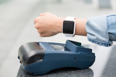 Woman paying the bill by smart watch