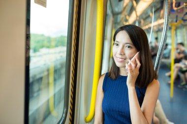 woman talking on cellphone inside train