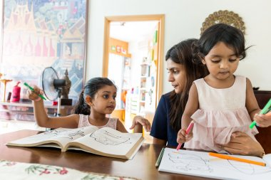 Indian family doing drawing on book