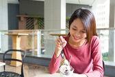 Asijské mladá žena jíst dezert