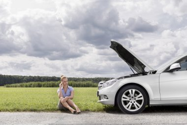 businesswoman sitting by broken down car