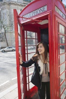 Woman opening door of telephone booth