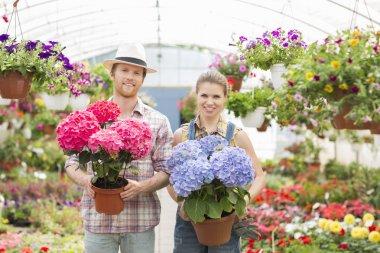 Gardeners holding flower pots