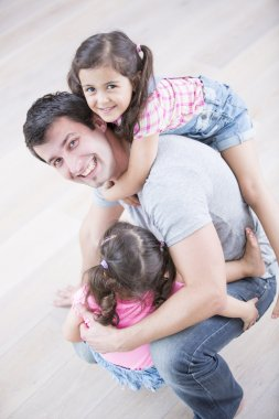 father carrying girls
