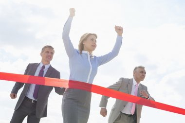 Businesswoman crossing finishing line
