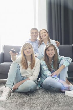 Family of four watching TV together