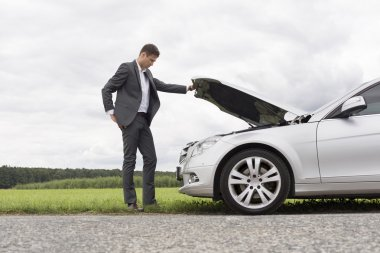 Businessman examining car engine