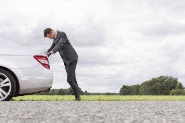 Businessman pushing broken down car