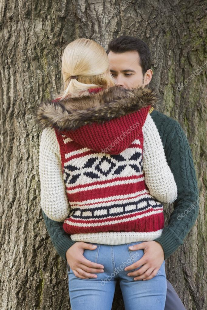 Couple standing against tree trunk