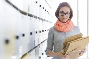 Businesswoman holding envelopes