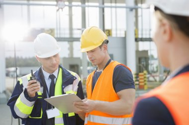 Workers discussing over clipboard