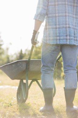 Male gardener pushing wheelbarrow