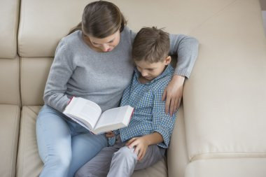 Mother and son reading book on sofa stock vector