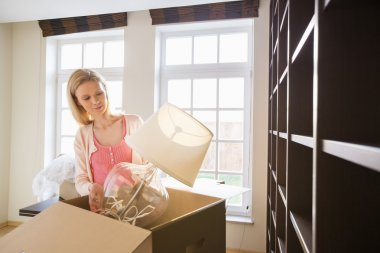 Woman removing lamp from cardboard box