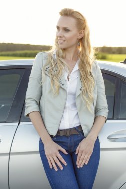 Woman looking away while standing by car