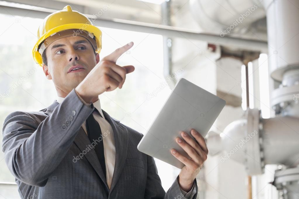 Young male engineer with digital tablet pointing away