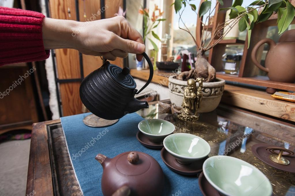 hand pouring tea into teacups