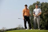 men standing with golf sticks