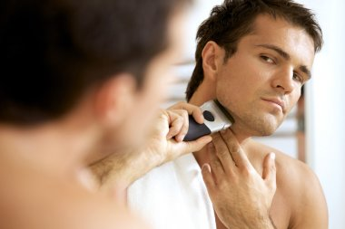 man shaving with electric shaver