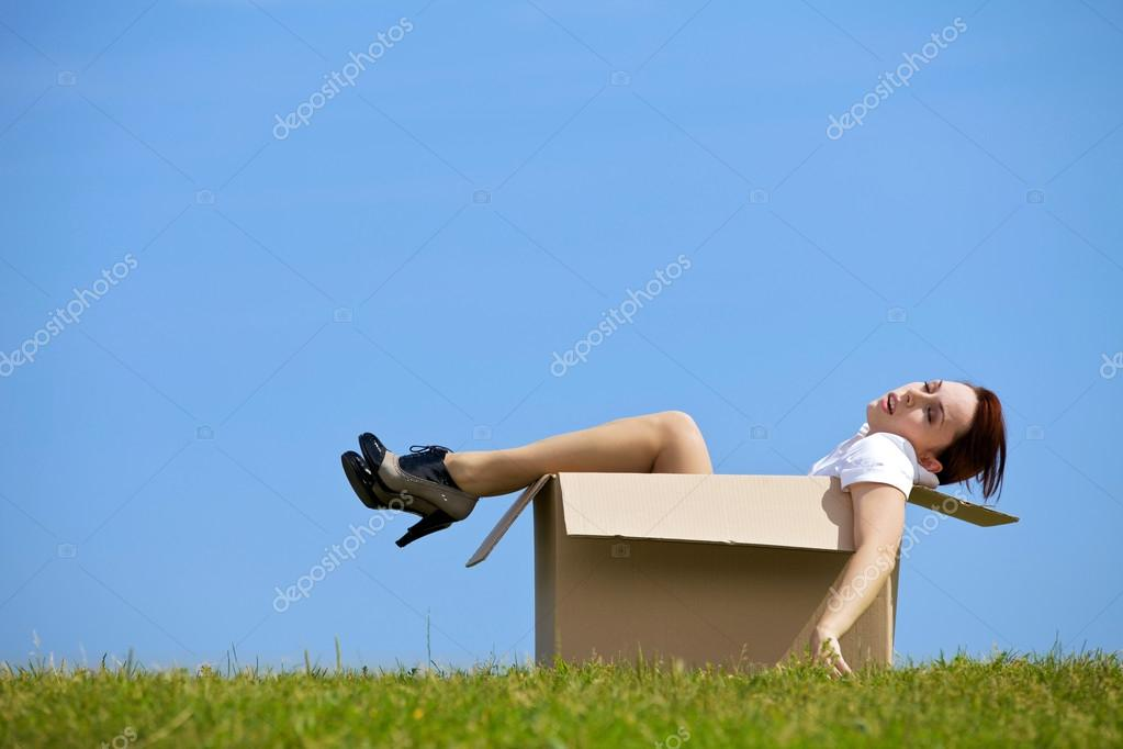 Woman relaxing in cardboard box