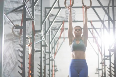 Woman exercising with gymnastic rings
