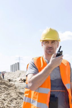 Confident supervisor using walkie-talkie