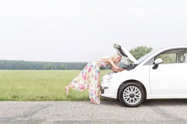 woman examining broken down car