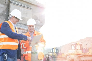 Happy supervisors discussing over clipboard at construction site against clear sky stock vector