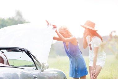 Friends examining broken down car
