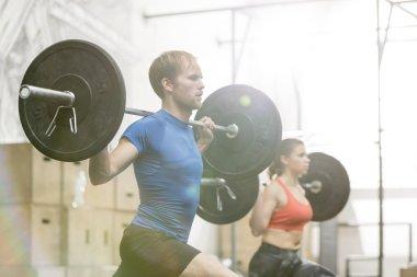 Man and woman lifting barbells