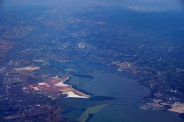 Aerial view of salt evaporation ponds, bridge, airports, cities