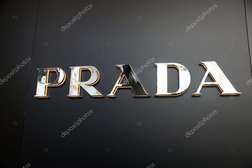 gold prada logo on black wall � stock editorial photo