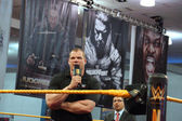Corporate Kane talks into mic with arms crossed in ring