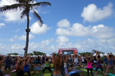 People raise arms over head during outdoor yoga class along the