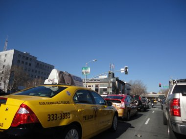 Cabs, Cars, and Trucks wait in traffic during red light
