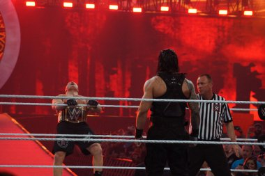 WWE Champion Brock Lesner screams as he leans back as he holds r