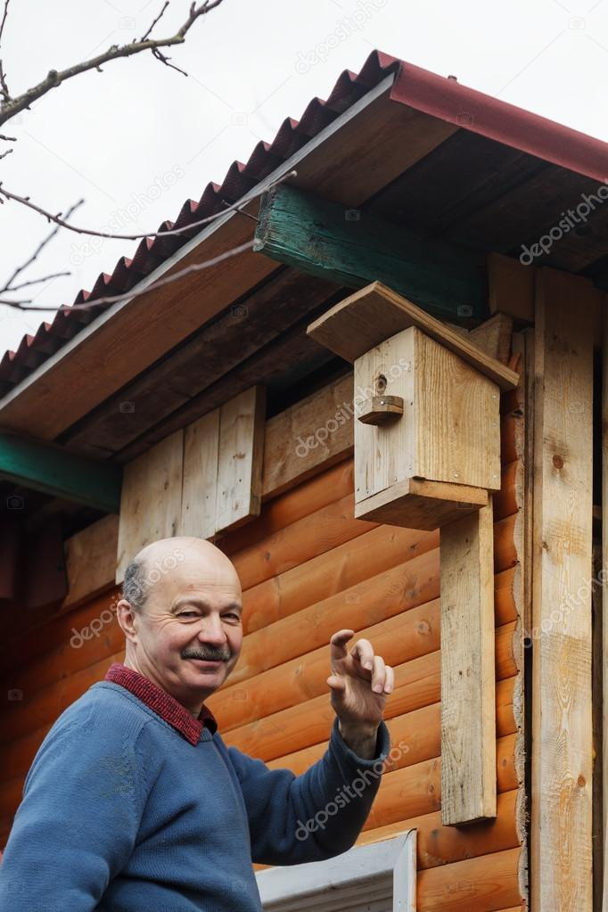 Bald senior with a mustache attaches birdhouse to the barn