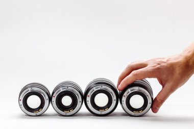 Man's hand adjusts a photographic lens. A collection of expensive toys for adults