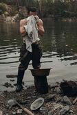 Fotografie Krankmeldung Goldgräber Handtücher mit Shirt nahe See mit felsigen bank