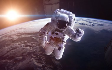 Astronaut in outer space against the backdrop of the planet earth. Elements of this image furnished by NASA