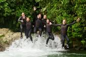 Photo Group Of Adult People Jumping Into Small Waterfall