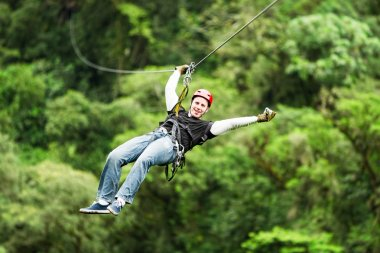 Adult Man On Zip Line Against Blurred Forest