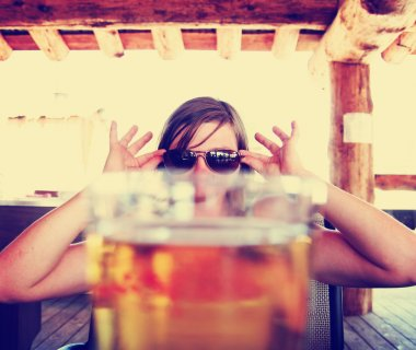 Woman peeking over draft beer
