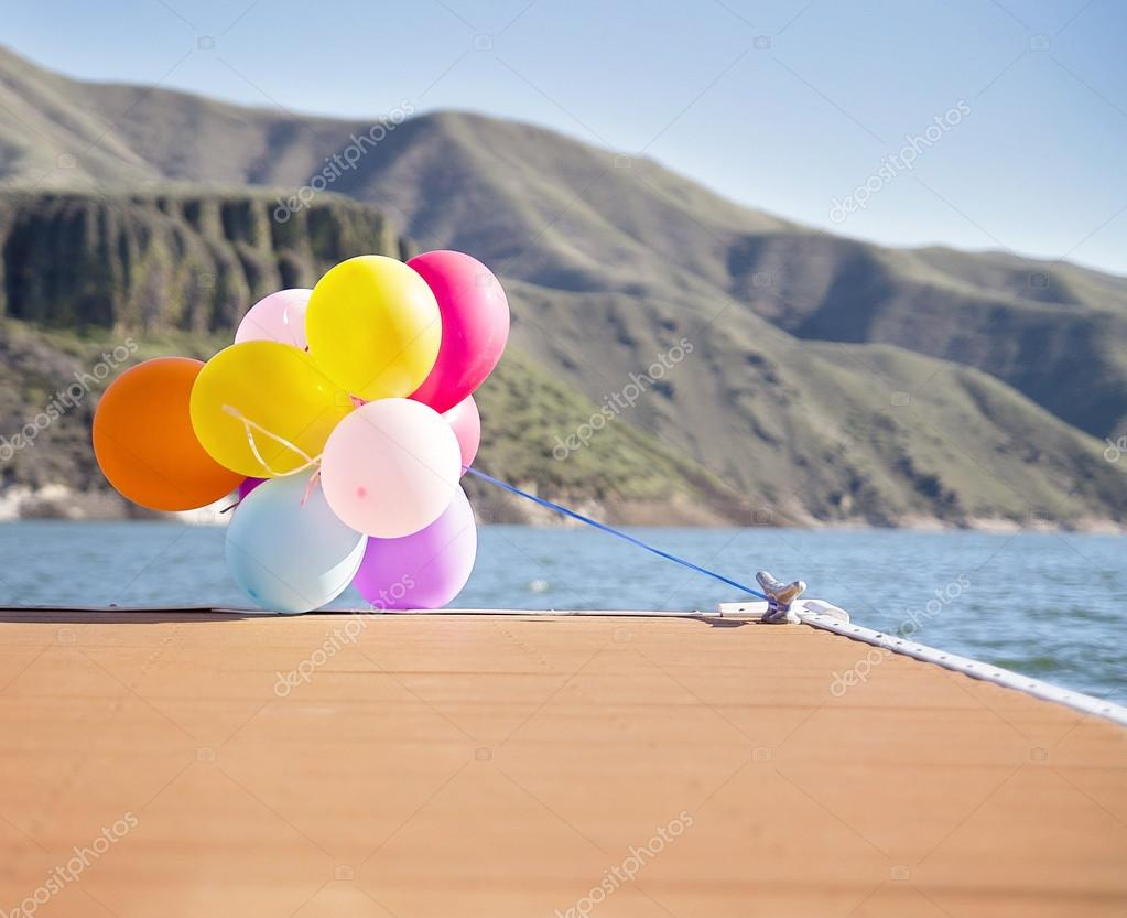Multicolored balloons tied to dock