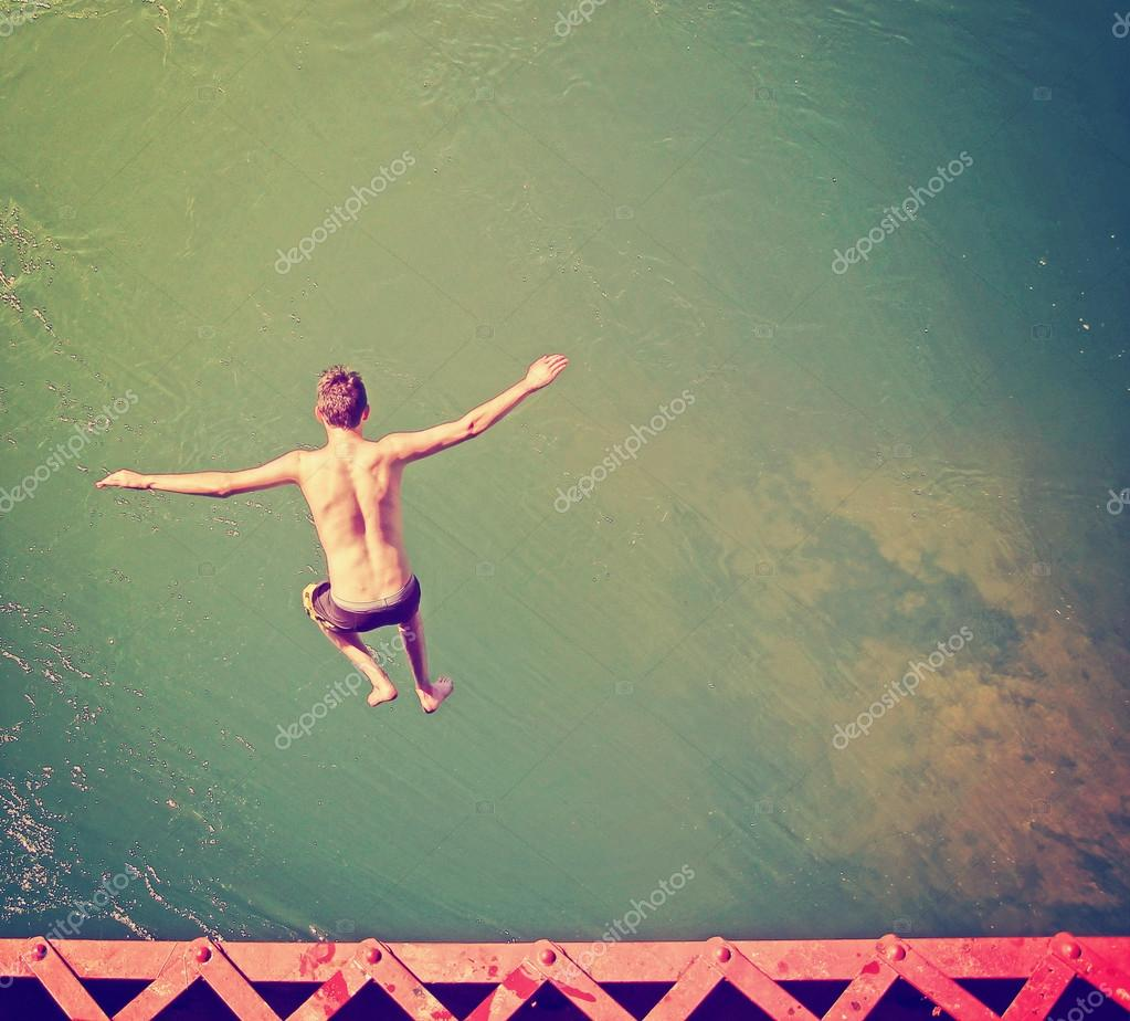 Boy jumping into river