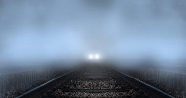 Train coming down tracks in fog