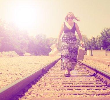 Girl walking down train tracks