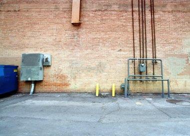 Refuse bin against old brick wall