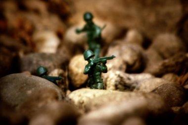 Miniature toy soldiers in desert battle scene.