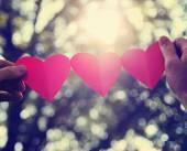 Ruce držící řetězec papírové srdce